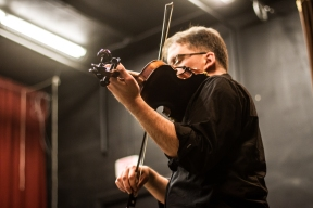 A fiddler plays live music at a contra dance. Photo by Sam Whited, used here under Creative Commons license with thanks.